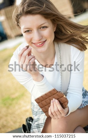 Lifestyle outdoor Young beautiful woman eating chocolate - lifestyle outdoor image - stock photo