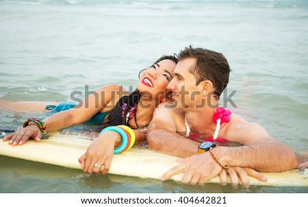 Lifestyle outdoors portrait of happy couple on surfboard in the ocean. Wearing stylish bikini, bracelets and flower necklace. On honeymoon. Young interracial couple in love, Asian woman, Caucasian man
