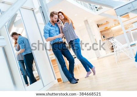 Lifestyle photo of couple in living room hugging and posing
