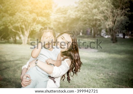 Lifestyle portrait mom and daughter in happines at the outside in the park - stock photo