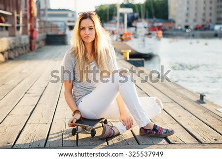 Lifestyle portrait of a young attractive woman sitting on a skateboard outdoors
