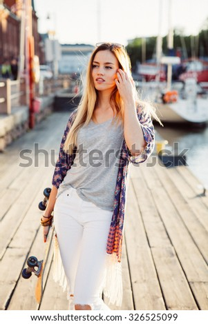 Lifestyle portrait of a young attractive woman with a skateboard in afternoon sun - stock photo