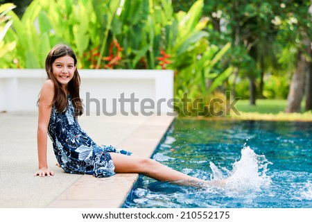 Lifestyle portrait of a young teen-aged girl at the swimming pool. - stock photo