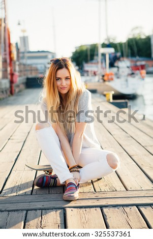 Lifestyle portrait of an attractive skater girl outdoors - stock photo