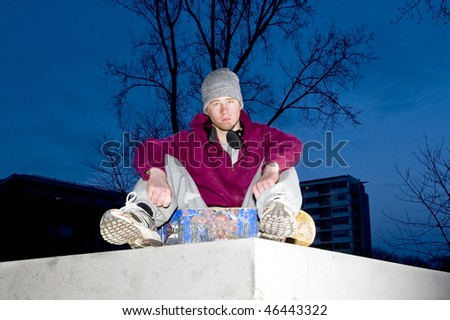 Lifestyle portrait of an unhappy looking youth with a skateboard in his hand sitting on the concrete ledge of a bunker - stock photo