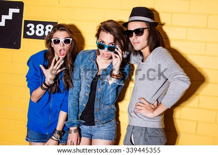 Lifestyle portrait of beautiful best friend hipsters wearing stylish bright outfits and sunglasses and having great time. Poses for the camera in front of yellow brick wall enjoying day and have fun. - stock photo