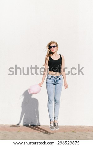 Lifestyle portrait of beautiful blonde girl having fun and jumping with cotton candy. Wearing sunglasses, red lips. Casual style, outdoors - stock photo