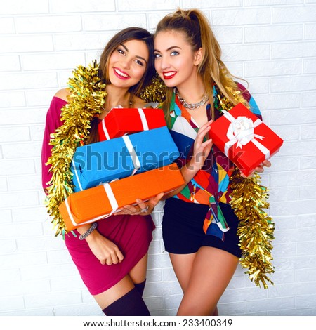 Lifestyle portrait of beautiful happy smiling funny best friends sisters, holding party gifts and presents. wearing trendy clothes and masquerade golden tinsel. White urban brick wall background. - stock photo