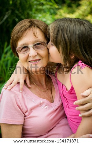 Lifestyle portrait of grandchild kissing grandmother - outdoor in nature - stock photo