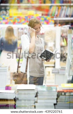 Lifestyle portrait of happy beautiful person using smartphone standing in bookstore and looking through books. Young model wearing casual clothing choosing book and making call. Vertical image - stock photo