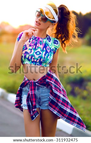 Lifestyle portrait of trendy woman in hipster outfit.Hiker Outdoor,fashion woman,crop top.Neon hat,cap,Sportive style,fall fashion,autumn look,crazy mood,stylish girl posing on sunset,sunshine woman - stock photo