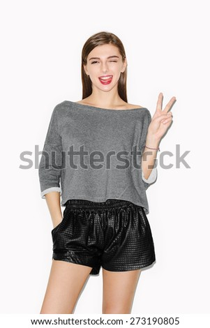 Lifestyle portrait of young attractive girl having fun. Natural makeup, red lips and casual style. White background, not isolated. Inside. - stock photo