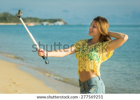 Lifestyle portrait of young lovely woman wearing a bright youth clothing, and making selfie with a stick against Samui beach. Having fun, joy and happiness.  - stock photo