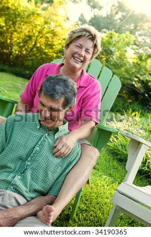 Lifestyle shot of happy mature couple relaxing in a sun-drenched outdoor setting.