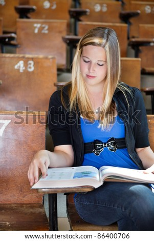 Lifestyle shot of young college girl reading a text book in a lecture hall - stock photo