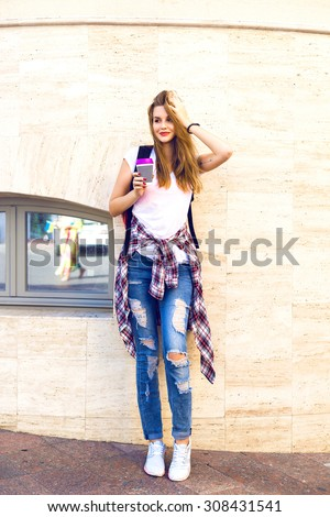 Lifestyle summer portrait of pretty blonde hipster woman, wearing street fashion casual outfit, denim and plaid shirt, blonde hairs and bright make up, drinking take away coffee, travel with backpack. - stock photo
