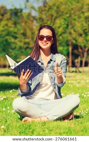 lifestyle, summer vacation, education, gesture and people concept - smiling young girl with book showing thumbs up and sitting in park - stock photo