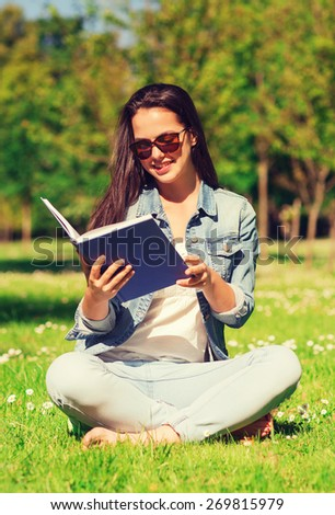 lifestyle, summer vacation, education, literature and people concept - smiling young girl reading book and sitting on grass in park - stock photo