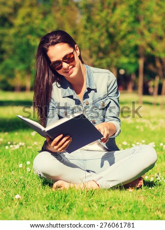 lifestyle, summer vacation, education, literature and people concept - smiling young girl reading book and sitting on grass in park