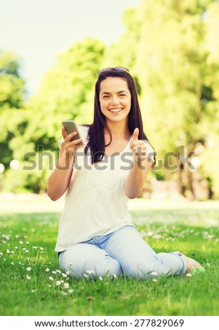 lifestyle, summer vacation, gesture, technology and people concept - smiling young girl with smartphone showing thumbs up in park - stock photo