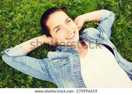 lifestyle, summer vacation, leisure and people concept - smiling young girl in blank white shirt lying on grass - stock photo