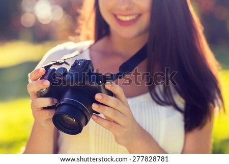 lifestyle, summer, vacation, technology and people concept - close up of young girl with photo camera outdoors - stock photo