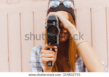 lifestyle sunny lifestyle fashion portrait of young stylish hipster woman walking on street,with video camera,smiling enjoy weekends,make a video of her travel,old retro videocamera,vintage  - stock photo