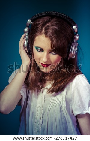 Lifestyle, young girl listening music with huge headphones - stock photo
