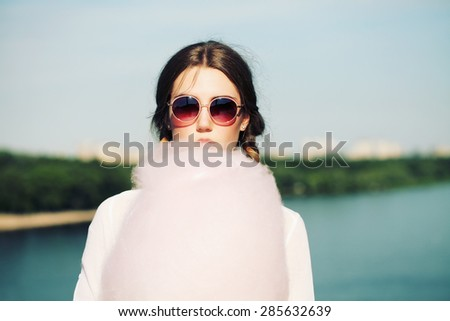 Lifestyle. Young happy hipster woman eating sweetened cotton candy, amazing view of the  river and the city from the bridge.  - stock photo