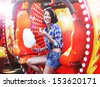 Lifestyle. Young Happy Woman Eating Sweetened Cotton Candy in Funfair - stock photo