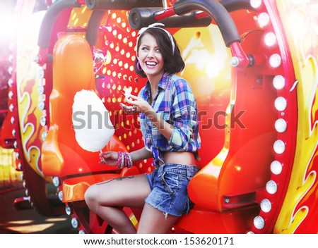 Lifestyle. Young Happy Woman Eating Sweetened Cotton Candy in Funfair