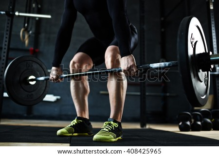 Lifting barbell in gym - stock photo