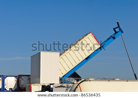 lifting cargo container at warehouse - stock photo