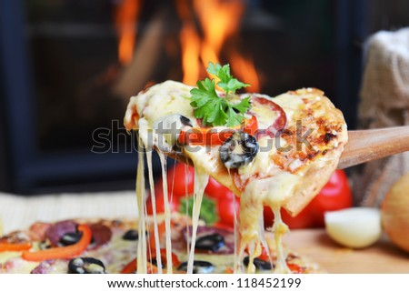 lifting slice of pizza with pepperoni and olives - stock photo