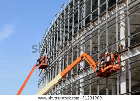 Lifts for workers on metal girders at a new construction site against blue sky - stock photo