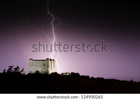 Lighnting strikes in a medieval castle in night landscape - stock photo