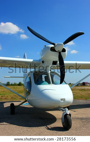Light aircraft against a blue sky - stock photo