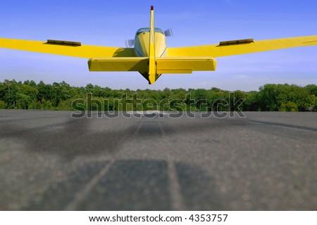 Light aircraft landing on a tarmac runway. - stock photo