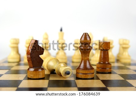 light and dark chess pieces on a chessboard on a light background