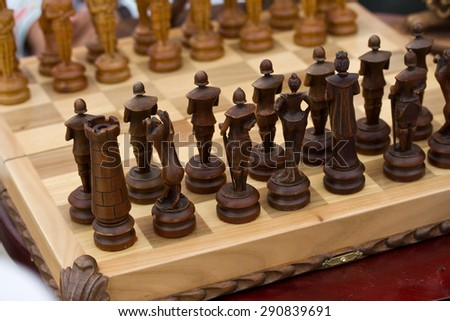 Light and dark wooden chess pieces on the board - stock photo