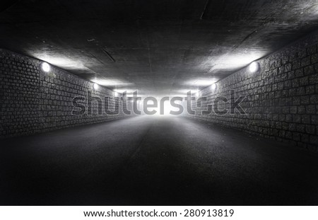 Light at the end of dark tunnel at night - stock photo