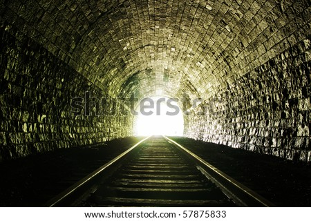 Light at the end of railroad tunnel. Natural lighting. - stock photo
