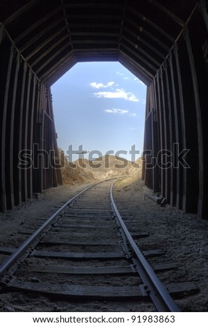 Light at the end of the tunnel. View inside a railroad tunnel - daylight, clouds, and mountains outside the opening.