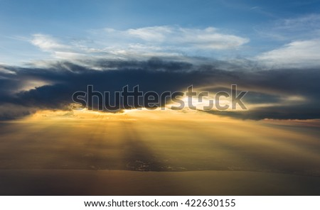 light beam of sunlight through clouds above sunset sky - stock photo