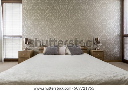 Light bedroom with decorative wallpaper and large double bed