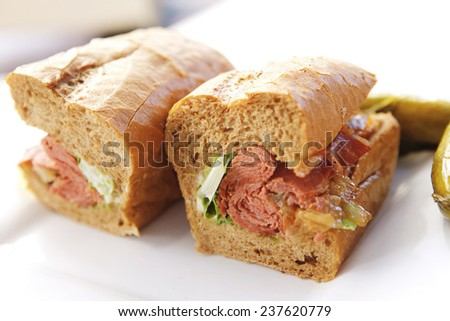 light beer and sandwich with beef and pork salami with snake on white table - stock photo