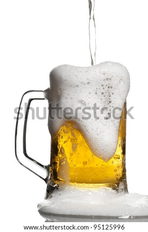 Light beer overflowing keg isolated on white