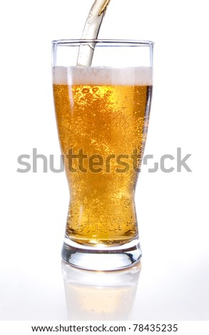 Light beer poured into glass on white background