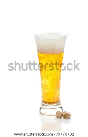 light beer with the foam in a tall glass and pistachios isolated on white
