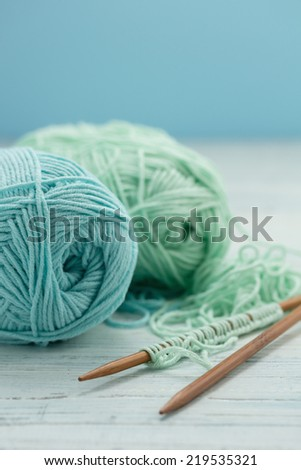 Light blue and green yarn with knitting needles - stock photo